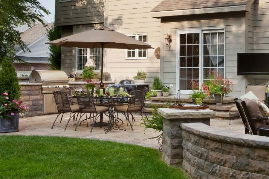 stone patio outdoor kitchen with an umbrella