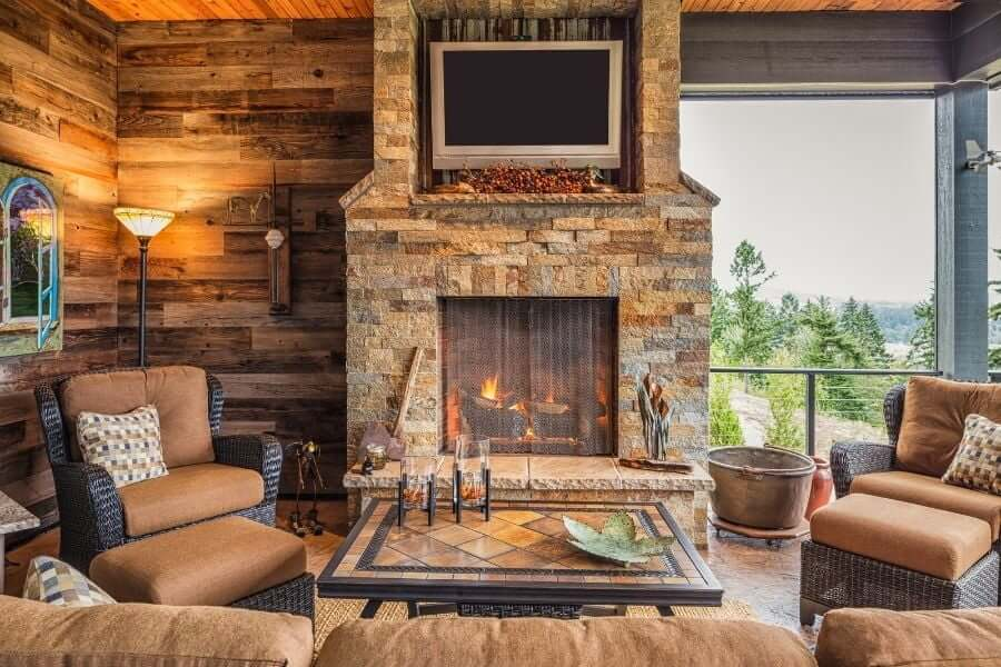 stone outdoor fireplace with a tv
