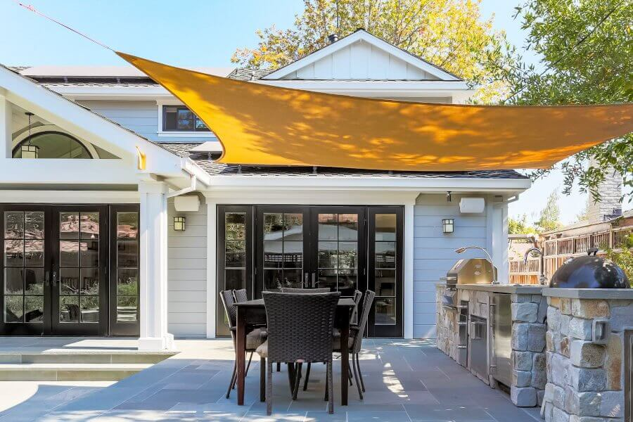 Patio outdoor kitchen covered with a sail shade
