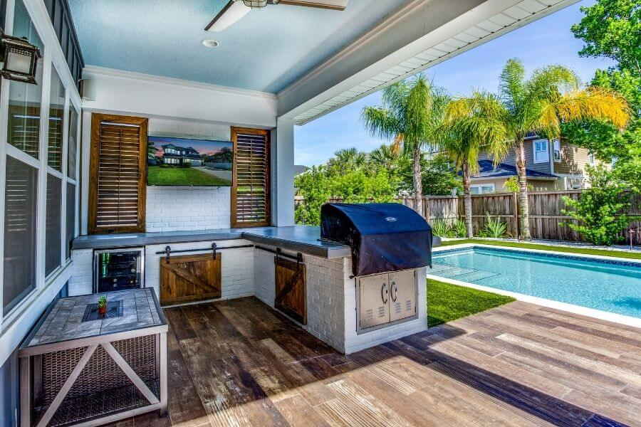 an l-shaped outdoor kitchen at the pool